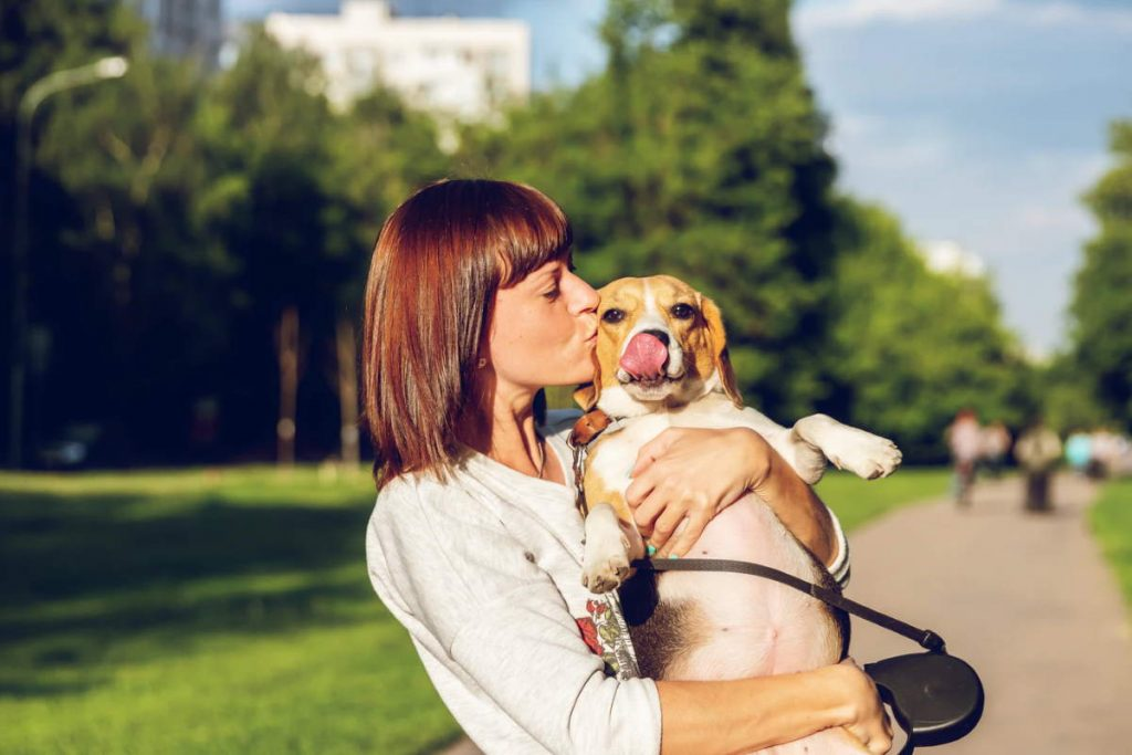 Woman holding and kissing her dog